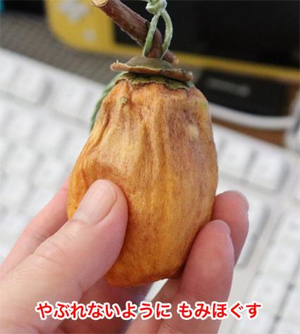 干し柿を指でもんで熟成させる
